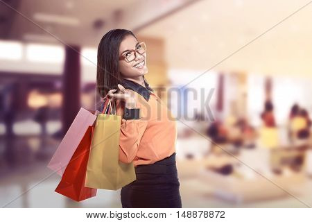 Happy asian woman holding shopping bags and smiling at the mall