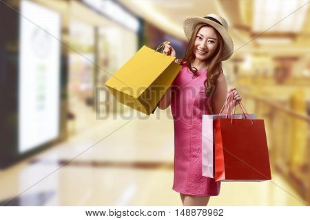 Happy Beautiful Asian Woman With Hat And Shopping Bags