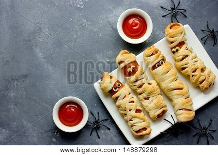 Halloween background. Funny sausage mummies with ketchup for Halloween. Top view