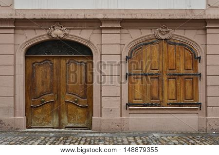 Basel Switzerland - September 18 2016: Dark wooden entrance gate next to closed windows on a pale pink residential building.