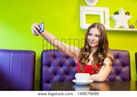 woman is taking selfie in a cafe. A mug of cofee on the table