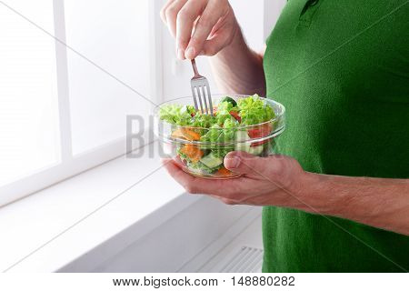 Man eat healthy lunch in modern interior. Unrecognizable profile male torso in green t-shirt, hand with fork, near window with vegetable salad in bowl, diet food concept. High key image