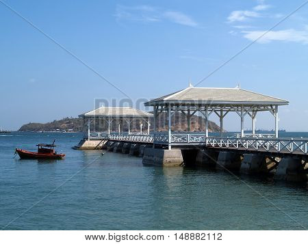 wooden bridge with antique pavilion and red boat floating in the sea, Assadang bridge, famous seascape viewpoint at Koh Sichang, Chonburi, Thailand
