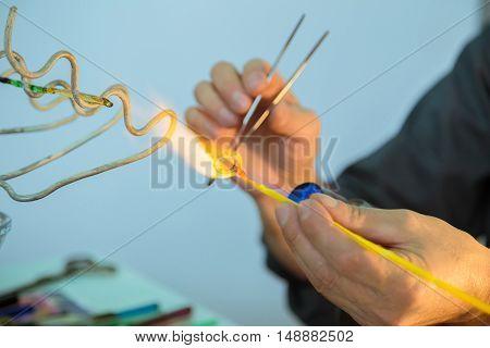 Artistic glassmaking. Glassblower makes blue glass ring