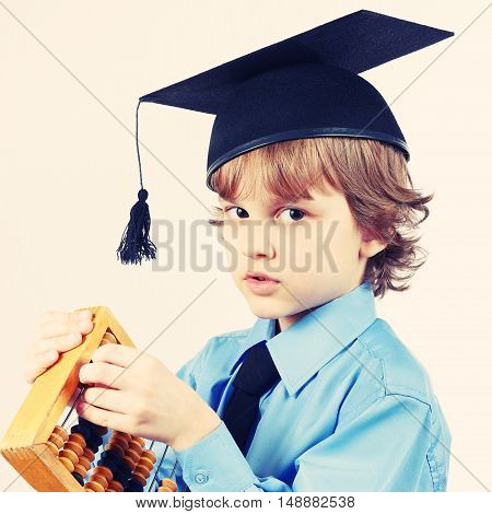 Little pensive boy in academic hat with old abacus on a light background gently toned