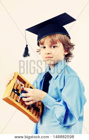 Little professor in academic hat with old abacus on a light background gently toned