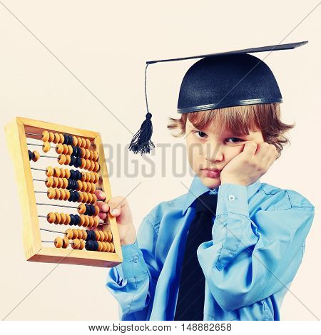 Tired boy in academic hat with old abacus on a light background gently toned