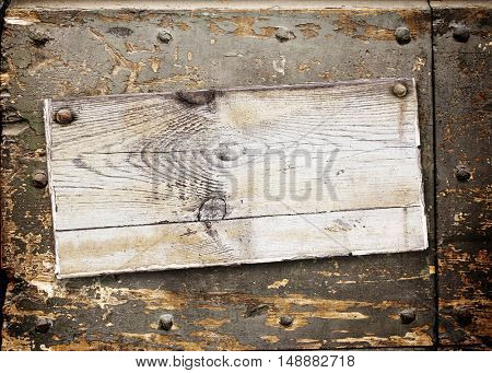 Old wooden board with cracked paint surface of grey color on wood wall of brown color