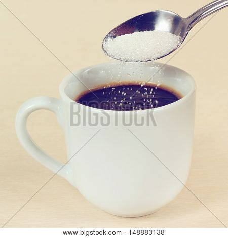Sugar is poured from a spoon in a coffee cup gently toned