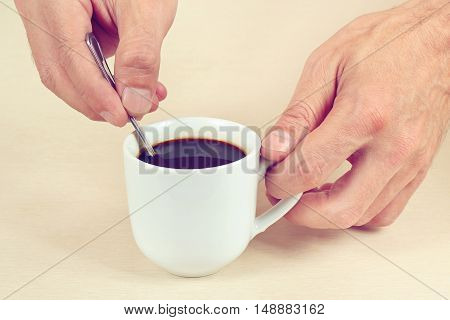 Hands mixing with a spoon of hot coffee in the cup gently toned