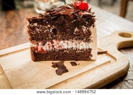 Close up Slice of chocolate cake with cherries topping on wood table.