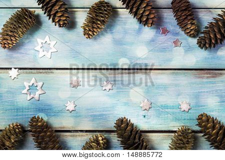 Winter, christmas background. Fir cones on a blue background vintage. With the overlay bokeh effect and snowflacks
