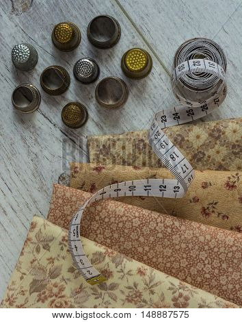 vintage cloth measuring tape old thimbles lie on a light wooden table. Top view