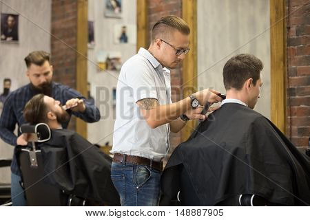 Interior shot of working process in barbershop. Back view of handsome young men getting trendy haircuts in modern barbershop. Cool male hairstylists serving clients poster