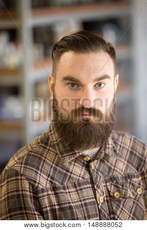 Headshot portrait of serious young man with long beard and mustache. Handsome bearded man posing with hands crossed on his chest looking at camera standing in his shop