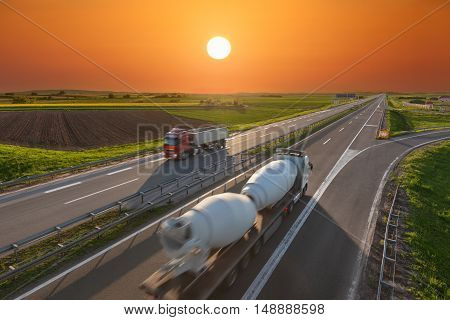 Two trucks for different purposes driving towards the sun. Fast blurred motion image on the freeway at beautiful sunset. Freight scene on the motorway near Belgrade Serbia.