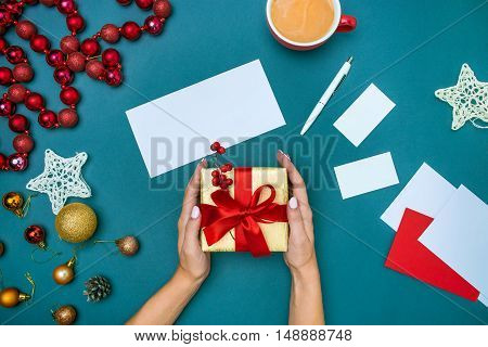 The hands of woman and Christmas gift box.
