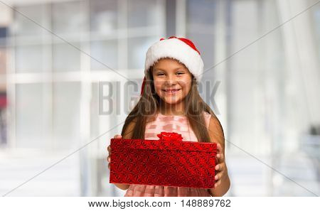 Smiling little girl holding a Christmas present