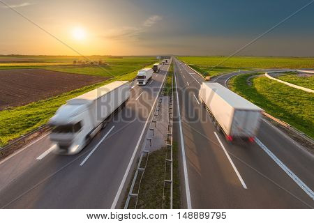 Many delivery trucks driving through agricultural fields. Fast blurred motion image on the freeway at beautiful sunset. Freight scene on the motorway near Belgrade Serbia.