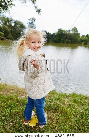 Blond girl at park at lake shore in autumn on a holiday