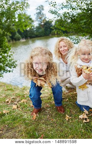 Girls having fun while collecting leaves in autumn in the nature