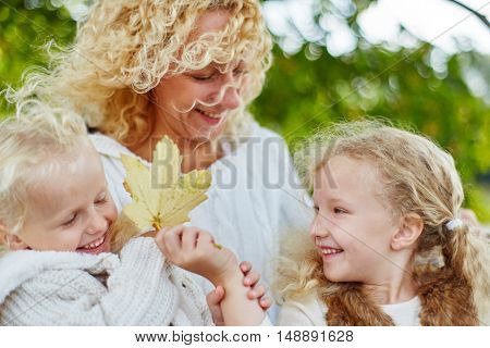 Sisters and mother playing with autumn leaves in the nature