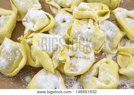 Pile of yellow raw ravioli with flour