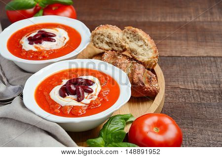Tomato cream soup with beans on wooden background, selective focus, copy cpace