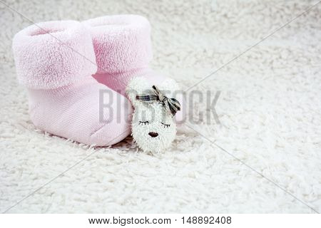 Two pink booties for babies with brooch as head of hare on the white fur