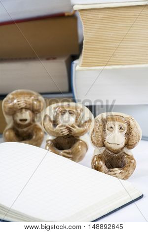 Three tired monkeys with notepad and many thick books as background
