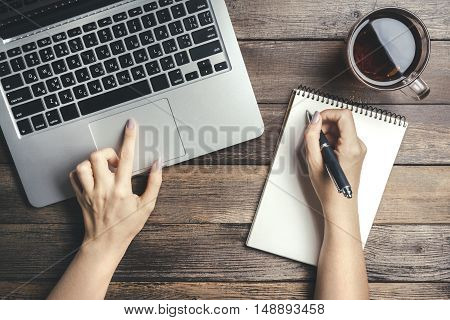 Female Hands Holding A Pan, Wrote In A Notebook And Typing On The Keyboard Of A Laptop On Vintage Wooden Table. Mock-up With Laptop, Cup And Pan On Notebook