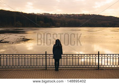 Lonely woman watching sunset alone in winter at sunset. Sad abstract concept of girl silhouette in love