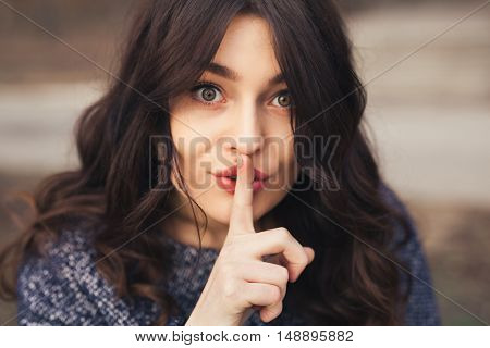 Young woman wearing autumn warm clothes keeping finger on her lips gesturing silent. Secret concept. Focus only on one eye.