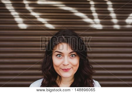 Beautiful brunette woman head surprised over street wall with copy space above head. Cute girl with big eyes smiling over graffiti brown background