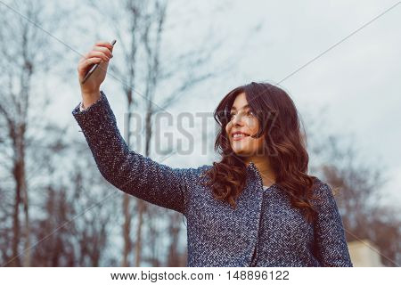Smiling lady taking selfie on autumn cold day. Young woman holding a smart phone trying to find network. Toned colors