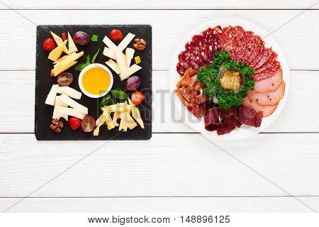 Cheese and meat plates on table, flat lay. Top view on two plates with variety of cheese and sausage snacks, free space