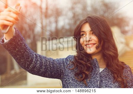 Beautiful fashionable girl taking a selfie with smartphone. Beautiful brunette young woman wearing a warm coat photographing herself on a autumn day. Retouched, vibrant colors and sun flares
