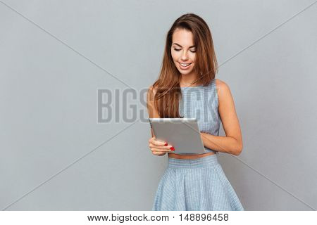 Happy beautiful young woman standing and using tablet over grey background