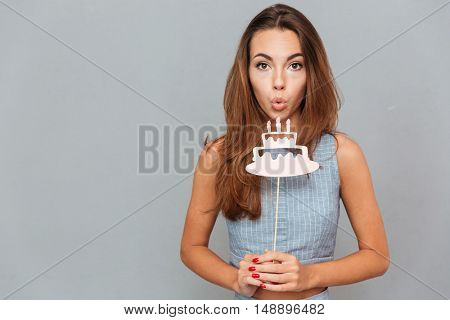 Pretty cute young woman blowing on birthday cake props over grey background