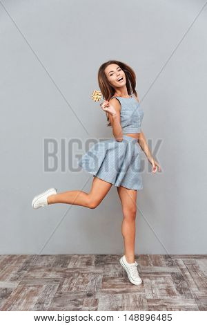 Full length of cheerful carefree young woman with lollipop running and jumping over grey background