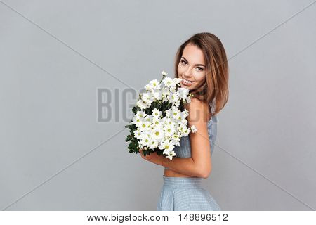 Cheerful charming young woman standing and holding bouquet of flowers over grey background