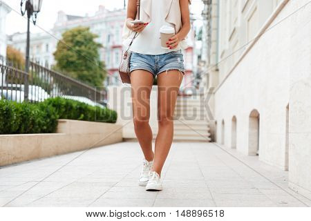 Cropped image of a young woman in denim shorts holding smartphone and coffee cup while walking on the street