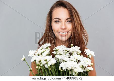 Portrait of smiling lovely young woman with bunch of white flowers over grey background