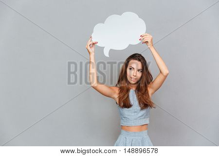 Thoughtful pretty young woman standing and holding blank speech bubble over grey background