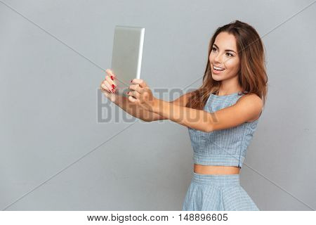 Smiling attractive young woman taking selfie with tablet over grey background