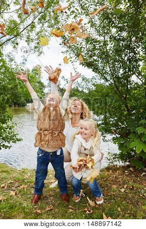 Kids throwing leaves in the air and have fun