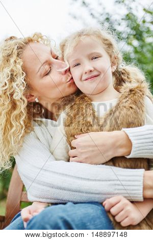 Happy mother kissing and embracing daugther with love in autumn