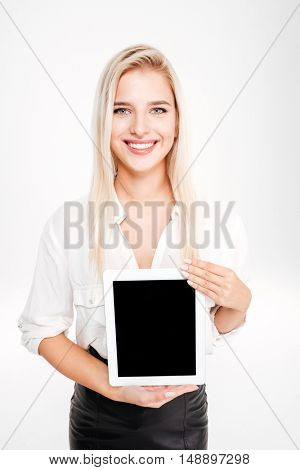 Smiling businesswoman showing tablet with blank screen isolated on the white background