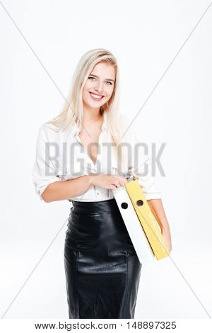 Happy young businesswoman standing and holding folders over white background