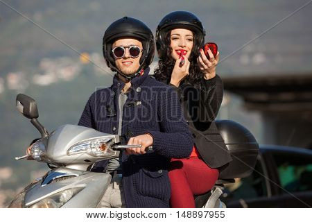 portrait of a young couple in scooter, she puts on lipstick